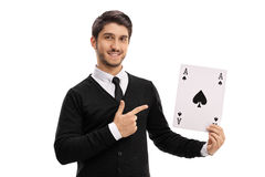Young man holding an ace of spades card and pointing. Isolated on white background Stock Images