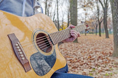 Young man holding acoustic guitar on bench in autumn park Stock Images