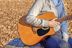 Young man holding acoustic guitar on bench in autumn park Royalty Free Stock Photos