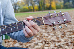 Young man holding acoustic guitar on bench in autumn park Royalty Free Stock Photography