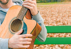 Young man holding acoustic guitar on bench in autumn park Royalty Free Stock Image