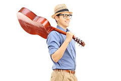 Young man holding an acoustic guitar over his shoulder Royalty Free Stock Photo