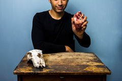 Young man holding an animal's heart next to a goat's skull Royalty Free Stock Photos