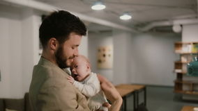 A young man is holding a baby on his arms and talking. Loft background stock video