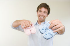 Young man holding baby slippers, smiling, close-up of hands (differential focus). Young men holding baby slippers, smiling, close-up of hands (differential focus Royalty Free Stock Images