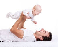 Young man holding baby son while lying on back Royalty Free Stock Photography