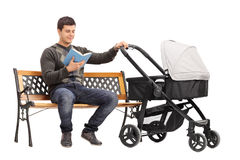 Young man holding a baby stroller and reading book. Isolated on white background Royalty Free Stock Image