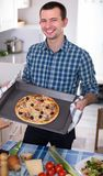Young man holding baking sheet with delicious pizza. Happy man holding baking sheet with delicious pizza in kitchen Royalty Free Stock Images