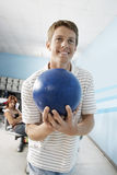 Young Man Holding Ball At Bowling Alley Stock Image