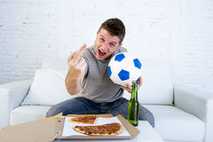 Young man holding ball watching football game on tv at home couch with beer celebrating crazy giving the finger. Young man holding ball watching football game on Royalty Free Stock Photography