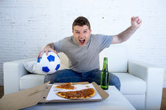 Young man holding ball watching football game on tv at home couch with pizza and beer celebrating crazy goal or victory Royalty Free Stock Photos