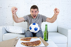 Young man holding ball watching football game on tv at home couch with pizza and beer celebrating crazy goal or victory Royalty Free Stock Image