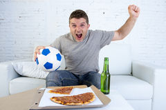 Young man holding ball watching football game on tv at home couch with pizza and beer celebrating crazy goal or victory Royalty Free Stock Photo