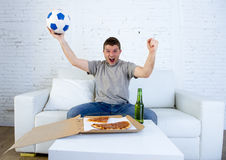 Young man holding ball watching football game on tv at home couch with pizza and beer celebrating crazy goal or victory Stock Photography
