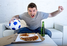 Young man holding ball watching football game on tv at home couch with pizza and beer celebrating crazy goal or victory Stock Photos