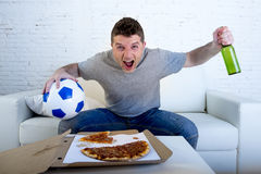Young man holding ball watching football game on tv at home couch with pizza and beer celebrating crazy goal or victory Royalty Free Stock Photography