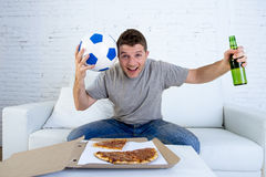 Young man holding ball watching football game on tv at home couch with pizza and beer celebrating crazy goal or victory Royalty Free Stock Images
