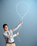 Young man holding balloon drawing Stock Photos