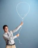 Young man holding balloon drawing Stock Photos