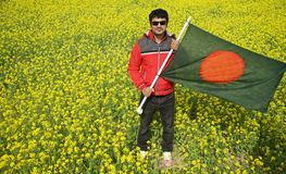Young man holding a Bangladeshi national flag in hand. Young man holding a Bangladeshi national flag standing around a mustard crops field isolated unique photo royalty free stock photos