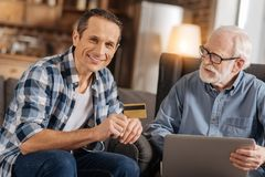 Young man holding bank card while his father using laptop. Enjoying online service. Pleasant young men holding a bank card, ready to pay for items online, and royalty free stock image