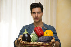 Young man holding a basket of fresh vegetables Stock Photo