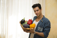 Young man holding a basket of fresh vegetables, healthy diet concept Stock Image