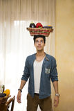 Young man holding a basket of fresh vegetables on his head Stock Image