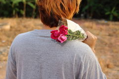 Young man holding a beautiful bouquet of red roses over shoulder on nature blurred background.  Stock Photo