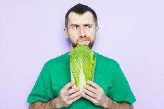 Young man holding Beijing napa cabbage in his hands. Doubt face expression. Light purple background stock photo