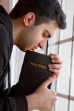 Man Praying by Window Stock Photo