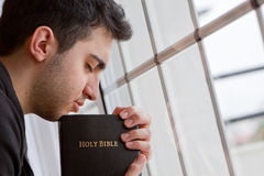 Man Praying by Window Stock Images