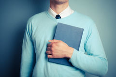 Young man holding a big book Stock Photography