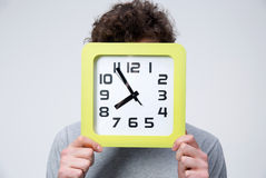 Young man holding a big clock covering his face Royalty Free Stock Photo