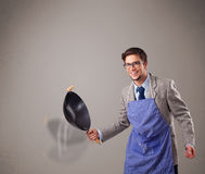 Young man holding a black frying pan Royalty Free Stock Images
