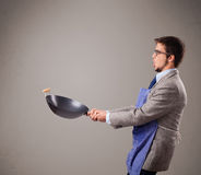 Young man holding a black frying pan Royalty Free Stock Photo