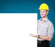 Young man holding blank billboard wearing hard hat. Portrait of Young man holding blank billboard royalty free stock photography