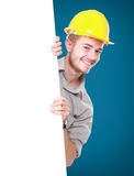 Young man holding blank billboard wearing hard hat Royalty Free Stock Images