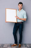 Young man holding blank board Royalty Free Stock Photo
