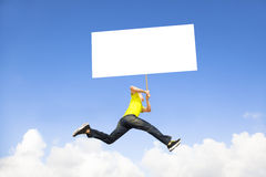 Young man holding blank board jumping Royalty Free Stock Images