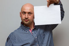 Young man holding blank form close-up. On a gray background Stock Photography