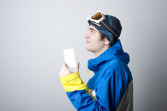 Young man holding blank lift admission ticket. Blank ski lift pass in hand of young man with winter outfit looking at corner. Concept to illustrate ski admission Stock Photography