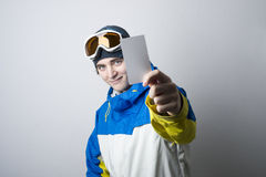 Young man holding blank lift pass. Young man holding blank ski lift pass looking. Concept to illustrate ski admission fee Royalty Free Stock Photo