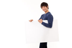 Young man holding a blank panel. Young Asian man holding a blank panel on white background Stock Photos