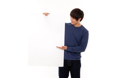 Young man holding a blank panel. Young Asian man holding a blank panel on white background Royalty Free Stock Photography
