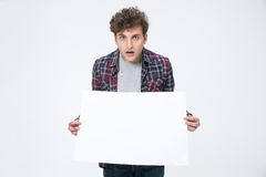 Young man holding blank paper. Portrait of a surprised young man holding blank paper Stock Photo