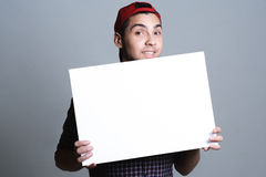 Young man holding blank paper in a studio Royalty Free Stock Images