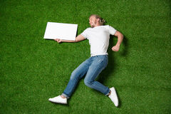 Young man holding blank placard while lying on meadow. Above view of young man holding blank placard while lying on meadow Royalty Free Stock Image