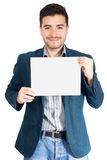 Young man holding blank poster. Hispanic man holding a white paper stock photography