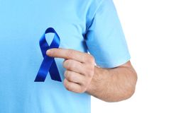 Young man holding blue ribbon on white background stock photos